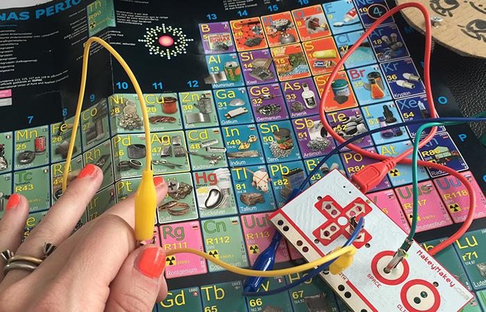 Programmeringsverktyget Makey Makey med sladdar på en bild av det periodiska systemet