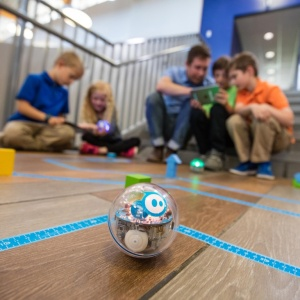Liten bollformad robot på golv, i bakgrunden barn och en vuxen sittandes på golvet